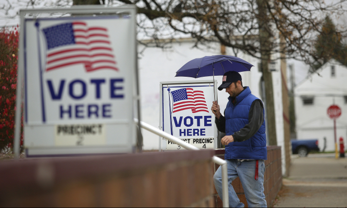 A man fills walks past voting signs displayed outside a polling station during the mid-term elections in Hamtramck, Michigan, on Nov. 4, 2014. (Joshua Lott/Getty Images)