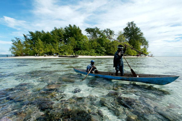 Fishermen paddle off Kennedy Island in the remote Western Province of the Solomon Islands, on July 28, 2003. (Torsten Blackwood/AFP/Getty Images)