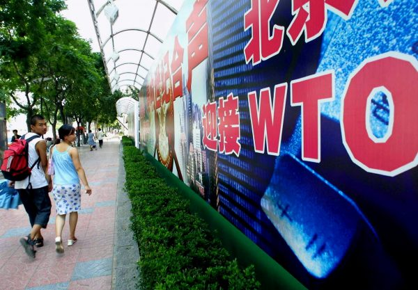 A young Chinese couple walk by a billboard promoting China's membership to the World Trade Organization (WTO), along a street in Beijing.
