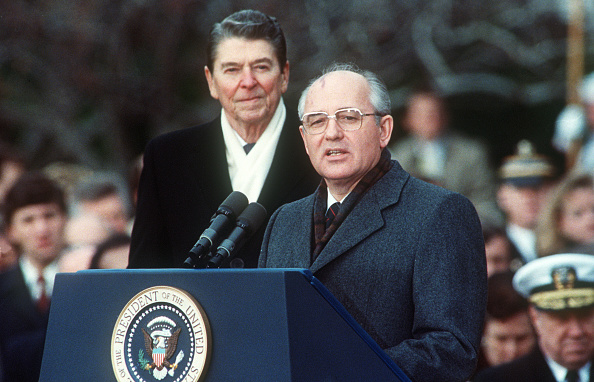 """US President Ronald Reagan (L) with Soviet leader Mikhail Gorbachev during welcoming ceremonies at the White House on the first day of their disarmament summit. After a three-day summit in Washington, both superpowers leaders put their names to the Intermediate-range Nuclear Forces (INF) Treaty in a first attempt to reverse the nuclear arms race.   Ronald Reagan, an icon to Republicans and a hero to those Americans who remember him as the man who brought down the """"Evil Empire"""". (JEROME DELAY/AFP/Getty Images)"""