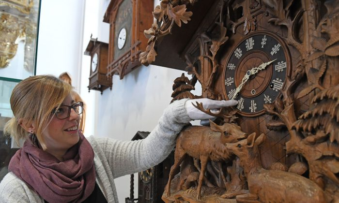 An employee moves the hands of a historic clock at the German Clock Museum in Furtwangen, Germany, on March 19, 2018. (Patrick Seeger/AFP/Getty Images)