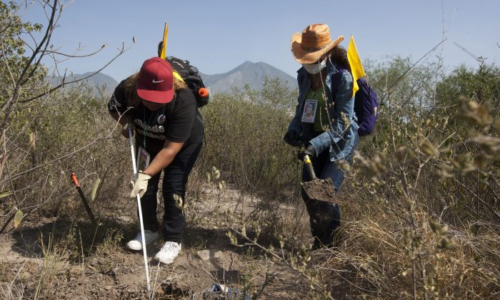 Two women work to find remains of missing people in Escobedo, Mexico, on Aug. 12, 2016. (Julio Cesar Aguilar/AFP/Getty Images)