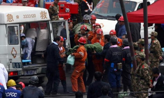 Workers wait outside the entrance to the Wangjialing coal mine as rescuers try to find more than 150 workers trapped in the flooded coal mine being built in northern China's Shanxi province on March 30, 2010. (Peter Parks/AFP/Getty Images)
