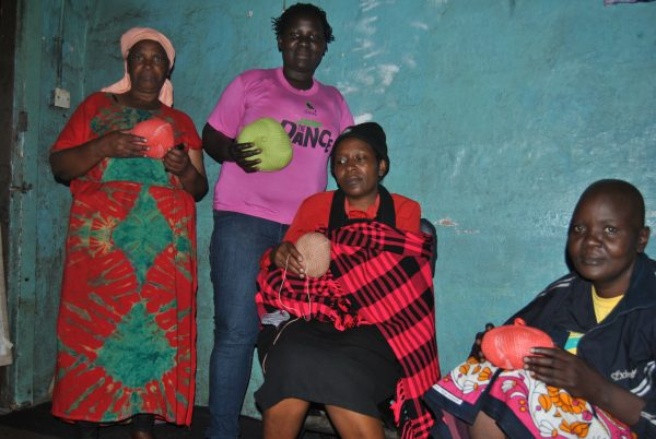 Cancer patients and survivors pose for a photo with knitted prosthetic breasts.