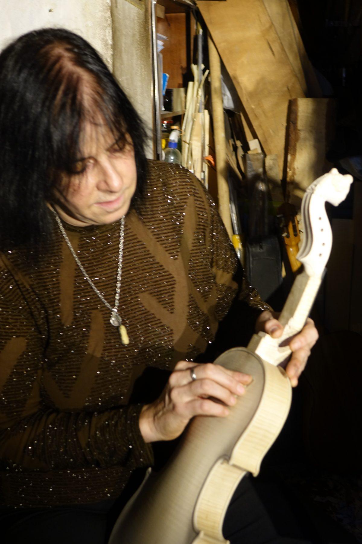 Violin maker sanding handmade violin