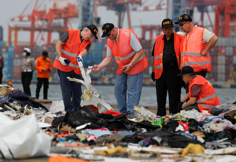 Personnel from National Transportation Safety Board examine debris from Lion Air flight JT610 at Tanjung Priok port in Jakarta