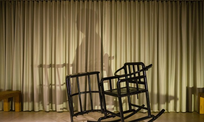 "This photo illustration shows the shadow of a person and a 'tiger chair', a restraining chair reportedly used by Chinese authorities when questioning detainees, on a stage in Hong Kong on Nov. 2, 2018. An art show by Chinese political cartoonist Badiucao, whose real-time image was going to be projected onto an avatar sitting in the chair, was cancelled due to safety concerns with organizers citing ""threats made by Chinese authorities relating to the artist."" (Anthony Wallace/ AFP/Getty Images)"