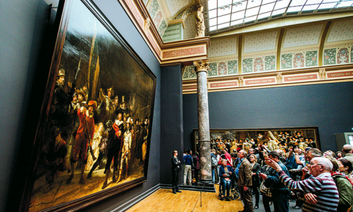"""Visitors look at Rembrandt's """"The Night Watch"""" in the Rijksmuseum in Amsterdam on May 17, 2015. (ROBIN VAN LONKHUIJSEN/AFP/GETTY IMAGES)"""