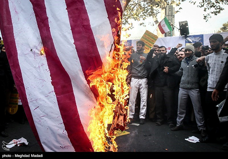 Iranian people burn the U.S. flag as they mark the anniversary of the seizure of the U.S. Embassy, in Tehran, Iran