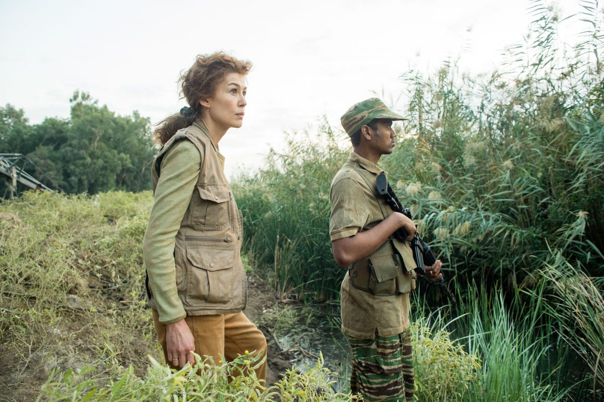 Rosamund Pike standing in war-torn countryside
