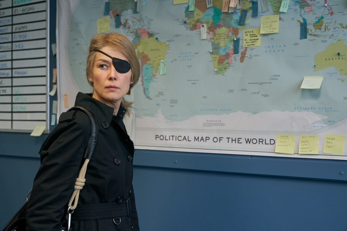 Rosamund Pike standing in front of map