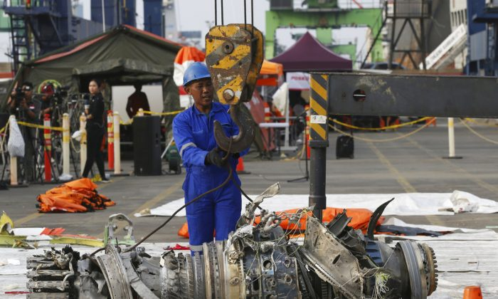 Officials move an engine recovered from the crashed Lion Air jet for further investigation in Jakarta, Indonesia, on Nov. 4, 2018. (AP Photo/Achmad Ibrahim)