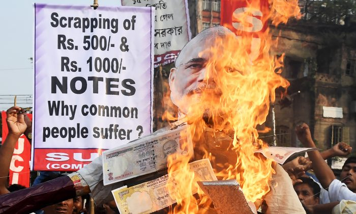 Protesters burn Indian prime minister Narendra Modi's effigy, decorated with posters of rupee notes, during a protest rally in Kolkata on Nov. 14, 2016.