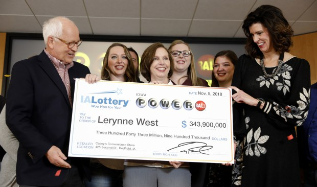 Iowa Lottery CEO Terry Rich, left, presents a check to Lerynne West, of Redfield, Iowa, center, for her share of a nearly $700 million Powerball prize, Monday, Nov. 5, 2018, at the Iowa Lottery headquarters in Clive, Iowa. West was one of two winners of a $688 million jackpot drawn Oct. 27. She'll share the prize with someone who bought the other winning ticket in New York City. (AP Photo/Charlie Neibergall)