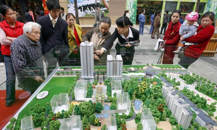 A saleswoman shows a housing model to customers in the southwestern municipality of Chongqing, China, on April 5, 2007. The Bank of Zigong in Sichuan Province could be facing financial troubles related to the city's reckless borrowing to fund infrastructure projects. (LIU JIN/AFP/Getty Images)