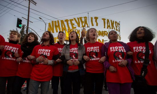 Striking McDonald's restaurant employees lock arms in an intersection before being arrested, after walking off the job to demand to demand a $15 per hour wage and union rights during nationwide 'Fight for $15 Day of Disruption' protests in Los Angeles, Calif, on Nov. 29, 2016. But only increased productivity can boost wages, not an edict by the government. (David McNew/Getty Images)