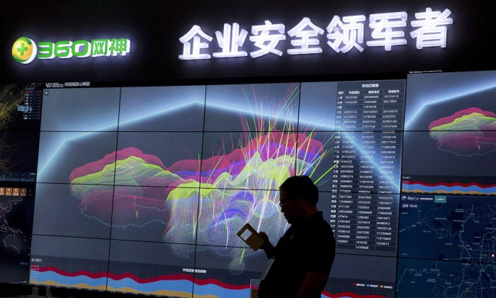 A worker is silhouetted against a computer display showing a live visualization of the online phishing and fraudulent phone calls across China in this file photo. China Telecom was caught employing a different method of cyber spying, namely diverting internet traffic. (AP Photo/Ng Han Guan, File)