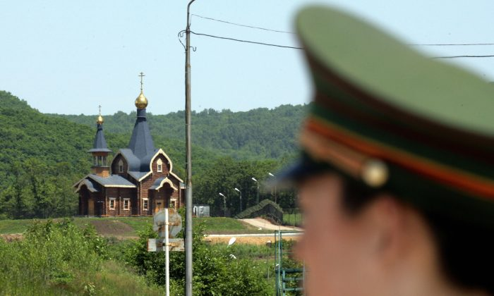 Suifenhe, CHINA:  A Chinese border guard stands watch at a border crossing with Russia at the Chinese border town of Suifenhe, northeastern Heilongjiang province 07 July 2006. (GOH CHAI HIN/AFP/Getty Images)