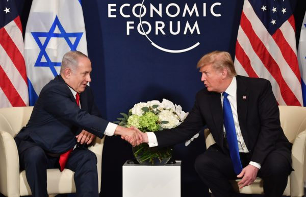 U.S. President Donald Trump (R) shakes hands with Israel's Prime Minister Benjamin Netanyahu in Switzerland.
