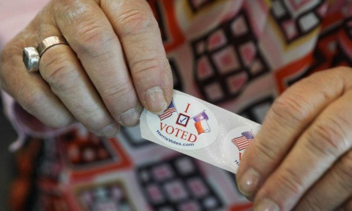 """A woman in Texas hands out """"I voted"""" stickers to voters at the Rummel Creek Elementary polling place in Houston, on Nov. 6, 2018. (Loren Elliott/Getty Images)"""