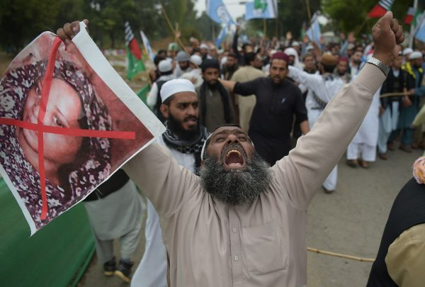 A Pakistani supporter of the Ahle Sunnat Wal Jamaat, a hardline religious party, holds an image of Asia Bibi