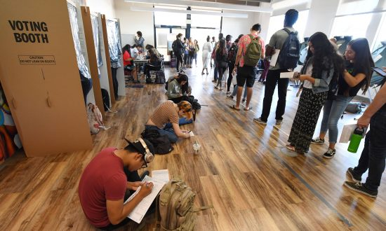 Students sitting on the floor of a polling station on the campus of the University of California, Irvine fill out provisional ballots as others wait in line to vote in Irvine, Calif. on Nov. 6, 2018. (ROBYN BECK/AFP/Getty Images)