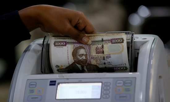 A Kenya Commercial Bank (KCB) worker counts Kenya shilling notes on a money counting machine as she serves a client inside in the banking hall at the Kencom branch in Nairobi on July 10, 2018. (Thomas Mukoya/Reuters)