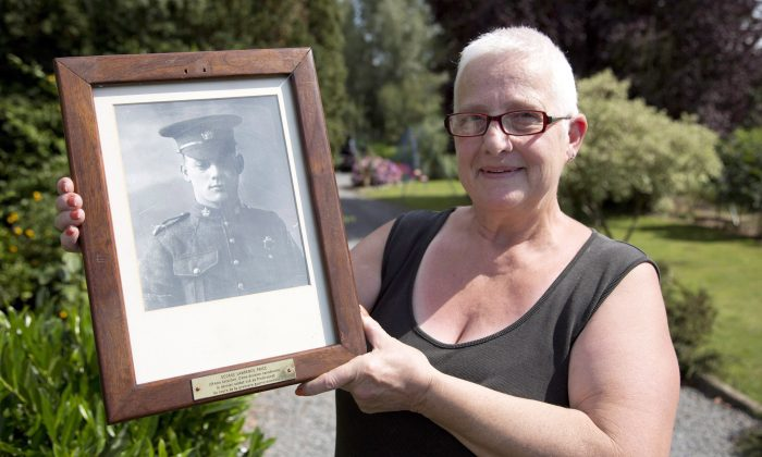 Marilyn Lahaeu with photo of World War I soldier Pvt. George Lawrence Price near her home in Ville-sur-Haine, Belgium on Sunday, Aug. 3, 2014. (Virginia Mayo/The Canadian Press/AP)
