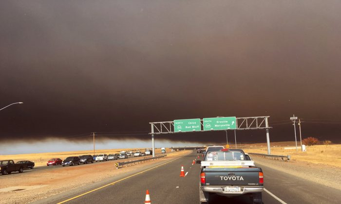 Smoke from the Camp Fire, burning in the Feather River Canyon near Paradise, Calif., darkens the sky as seen from Highway 99 near Marysville, Calif., on Nov. 8, 2018. (AP Photo/Don Thompson)