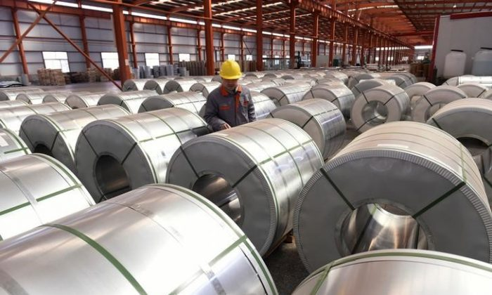 A worker checks aluminum rolls at a warehouse inside an industrial park in Binzhou, Shandong Province, China on April 7, 2018. (China Daily via Reuters)