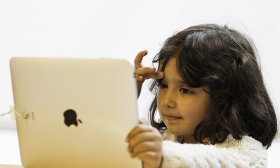 A girl uses an iPad at an Apple store in central London in this file photo. (Reuters/Luke MacGregor)