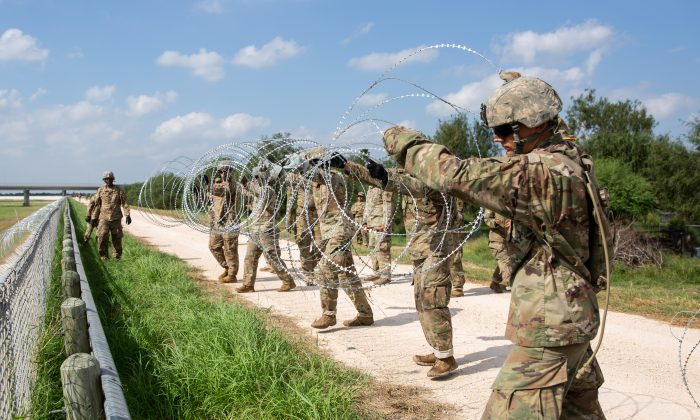 The U.S. military installs concertina wire on the levee behind Granjeno in Texas, just north of the U.S.-Mexico border on Nov. 7, 2018. (Samira Bouaou/The Epoch Times)
