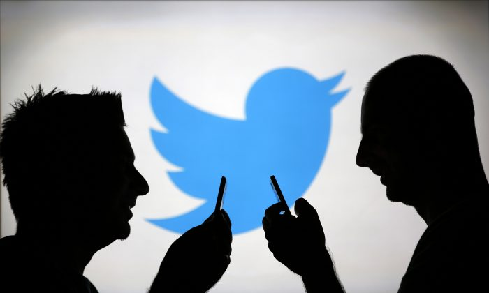 Men are silhouetted against a video screen with a Twitter logo in the Bosnian town of Zenica, on Aug. 14, 2013. (Dado Ruvic/Reuters)