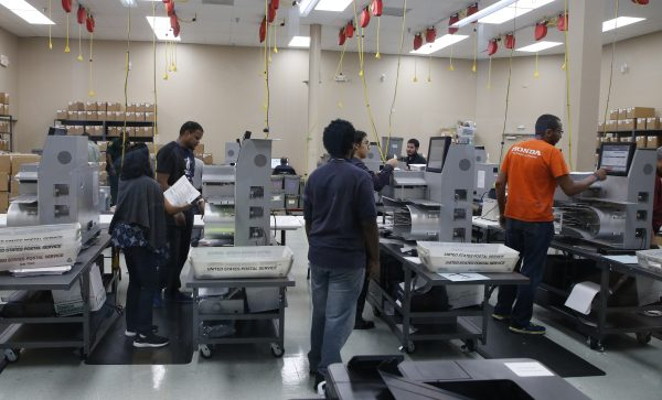 Elections workers feed ballots into tabulation machines at the Broward County Supervisor of Elections office in Lauderhill