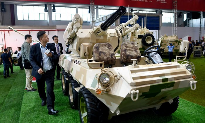 """Visitors look at a """"wheeled combat vehicle"""" on display at Airshow China 2018 in Zhuhai in southern China's Guangdong Province on November 7, 2018. (Photo by WANG ZHAO / AFP)        (Photo credit should read WANG ZHAO/AFP/Getty Images)"""