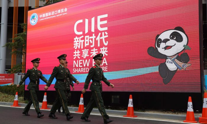 Chinese paramilitary policemen march near a billboard for the China International Import Expo in Shanghai on Nov. 4. Visitors to the vast trade fair, meant to rebrand China as a welcoming import market, could sip Moroccan wine, ogle Italian yachts, and watch a Japanese industrial robot play Ping-Pong. (AP Photo/Ng Han Guan)