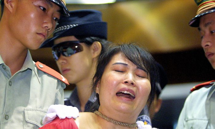 Convicted drug pedlar Wang Xiongyin breaks down as she Is sentenced to death for selling 200 grams of heroin for 27,000 yuan back in 1999, in Guangzhou, 26 June 2003, as China marks the International Anti-Drugs Day. (STR/AFP/Getty Images)