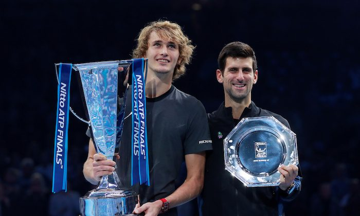 First placed Alexander Zverev of Germany and second placed Novak Djokovic of Serbia pose for photographs with their trophies after the final   Action, London, Britain, on Nov. 18, 2018.    (Reuters/Andrew Couldridge)