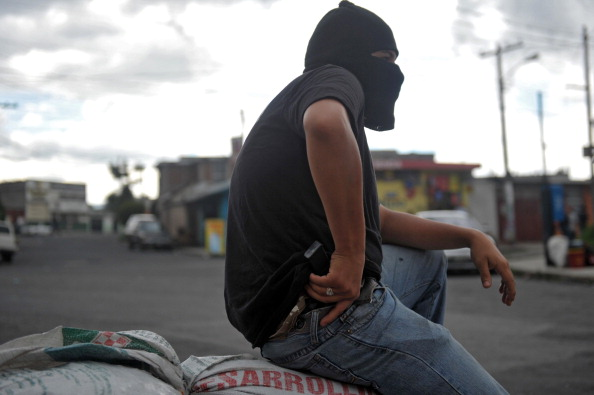 A hooded man holding a gun stands guard in the entrance of the Castanas neighborhood, in the southern outskirts of Guatemala City to prevent an attack by a local gang in this file photo. The residents of Castanas have been threatened and extorted by gang members organized their own armed gang in self defense. Contrary to the intended purpose, U.S. aid is helping gangs and hurting honest citizens in Guatemala. (JOHAN ORDONEZ/AFP/Getty Images)