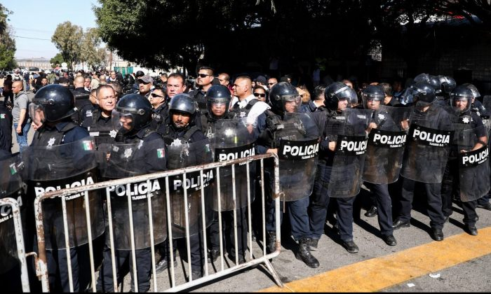 Tijuana riot police form a barrier between the migrant camp and protesting Mexicans in Tijuana, Mexico, on Nov. 18, 2018. (Charlotte Cuthbertson/The Epoch Times)