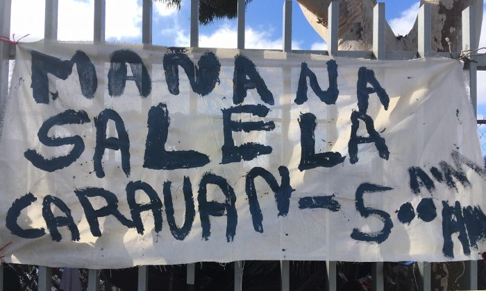 """A hand painted sign that says """"The caravan leaves at 5 a.m. on Sunday"""" on the fence around the sports complex where up to 5,000 migrants are camping out in Tijuana Mexico, on Nov. 24, 2018. (Charlotte Cuthbertson/The Epoch Times)"""