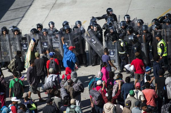 Central American migrants are blocked by Mexican police forces as they reach the El Chaparral border crossing, in Tijuana, Baja California State, Mexico