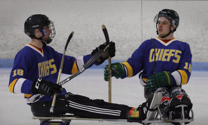 Humboldt Broncos hockey player Jacob Wassermann (L) and teammate Ryan Straschnitzki compare sticks during a sled hockey scrimmage at the Edge Ice Arena in Littleton, Colo., on Nov. 23, 2018. (The Canadian Press/Joe Mahoney)