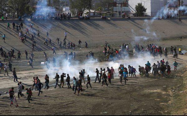 Migrants run from tear gas, thrown by the U.S. border patrol,