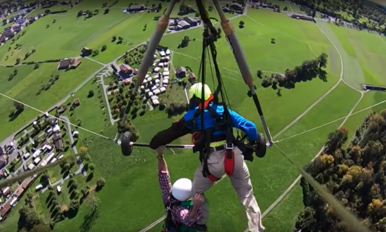 YouTuber Chris Gursky hangs from the bar of the hang-glider and his pilot's leg over the Swiss countryside in Oct. 2018. (Screengrab/YouTube/Chris Gursky)