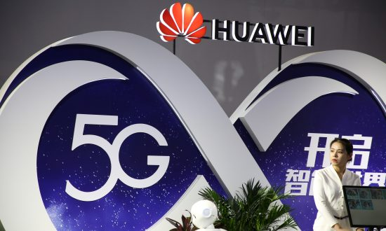 A woman stands at the booth of Huawei featuring 5G technology at the PT Expo in Beijing on Sept. 28, 2018. (Reuters)