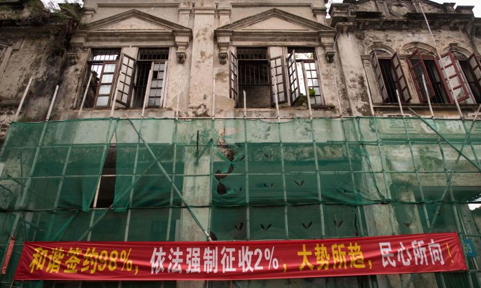 """In this picture taken on May 28, 2018, a banner that reads """"98 percent of people have signed contracts in a pleasing way, 2 percent of peoples houses have been forced-collected according to law, its the trend of the time and coinciding with the popular will"""" is seen on a building in Chikan village in Kaiping. (NICOLAS ASFOURI/AFP/Getty Images)"""