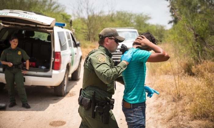 File photo showing a U.S. Border Patrol agent patting down a man who crossed the Rio Grande illegally, in Hidalgo County, Texas, May 26, 2017. (Benjamin Chasteen/The Epoch Times)