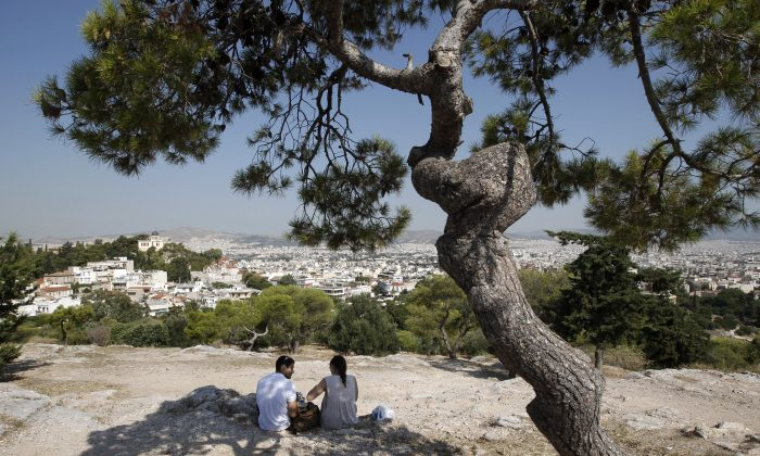 Tourists sit under a pine tree on a hill overlooking Athens on July 7, 2011. (Reuters/John Kolesidis)