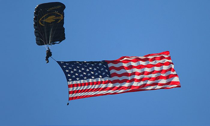 A file photo of a member of the U.S. Army Jump Team displaying the flag while descending over Sebring International Speedway in Florida before a race. (Chris Jasurek/The Epoch Times)